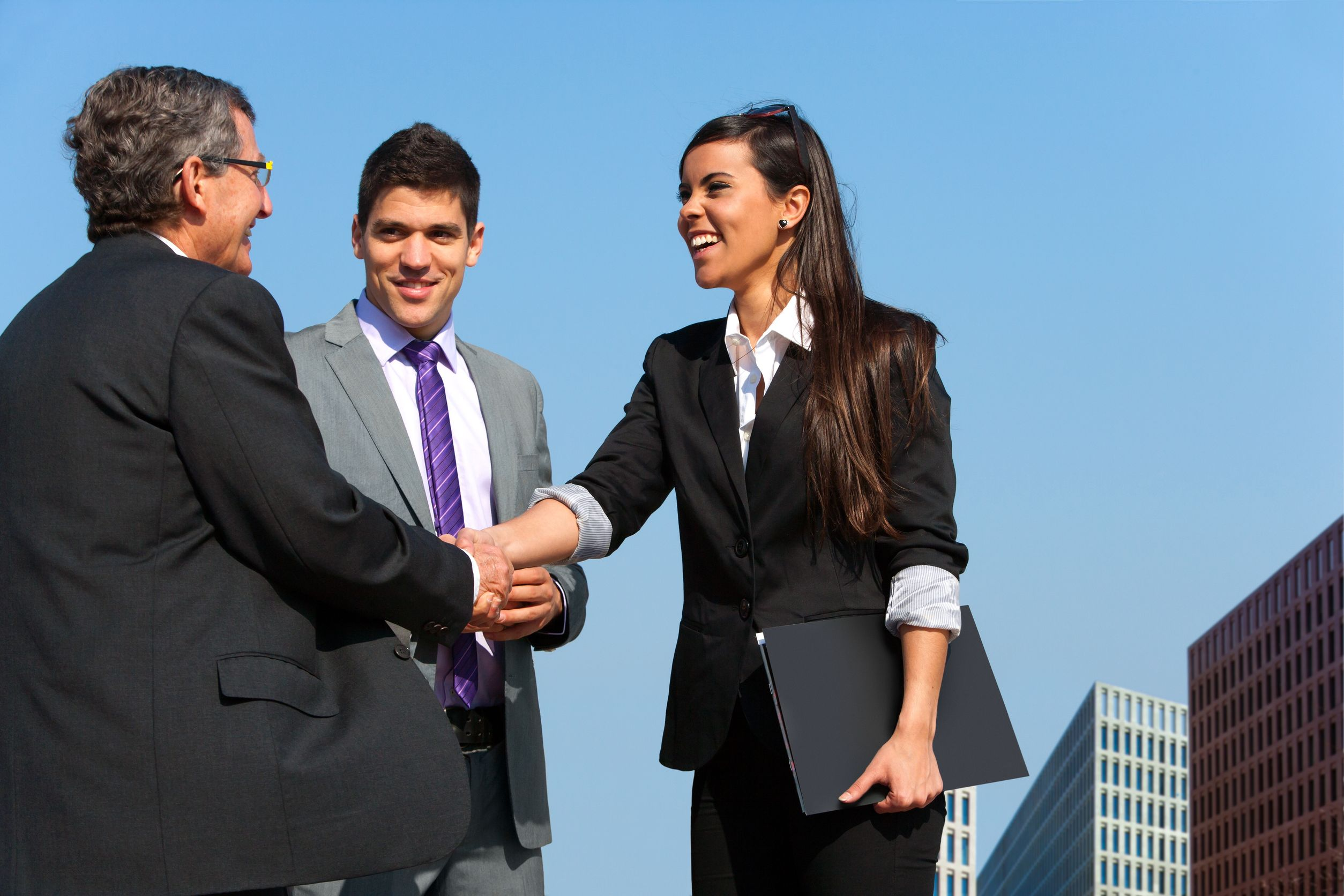 13686659 – young business couple shaking hands with partner outdoors.